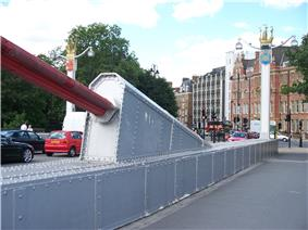 End of a large red suspension cable, attached to a protrusion atop the side of the bridge deck.