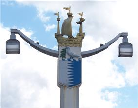 Post holding two lamps at the ends of two arms. The top of the post is decorated by a galleon; underneath the boat is a shield containing a white left and a blue right separated by a jagged line, on top of which rests a white bird carrying an olive branch.