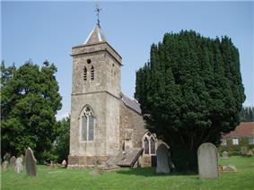 Gray stone building. Prominent square tower with arched window, topped by small slate pyramidal roof. Left and right of the building are yew trees amongst gravestones.