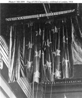 A black-and-white photo of a battle-worn flag suspended from the ceiling of a museum