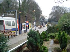 A grey railway platform with a series of light poles surrounded by brown trees, green bushes, and yellow and white flowers all under a white sky