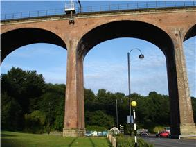 A large railway viaduct made from red bricks, topped by railings and electric pylons