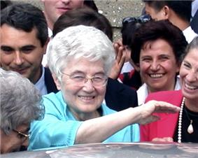 Chiara Lubich, smiling, surrounded by other smiling people