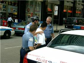 A man on a city street in a white shirt with his hands cuffed behind his back, with three police officers behind him. The one at rear is opening the door of the police car in the bottom right of the image.