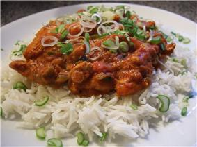 A dish of rice (white) with Karai chicken (dark orange) on it in a plate