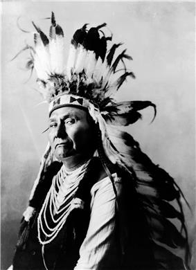Profile of the head and torso of a dignified man of about the age 60. He wears a headpiece featuring many long white feathers with black tips. His shirt or upper garment is dark, though its sleeves are white. Decorative parallel ovals of a white material extend down the front of this garment from neck to midriff.