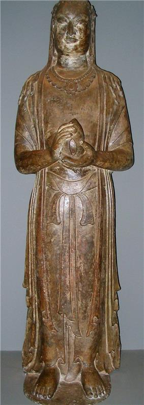 A standing Buddha: a yellow statue made from limestone, with its hands in prayer and holding a lotus
