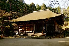 Wooden building with a hipped roof, slightly raised floor, an enclosing veranda and a wide central staircase on the front.