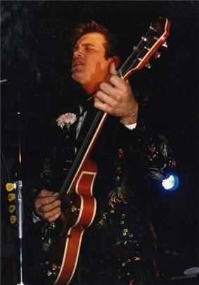 A man singing and playing a guitar