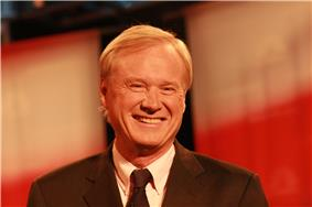 A smiling man with blond hair wearing a gray suit jacket and black tie.