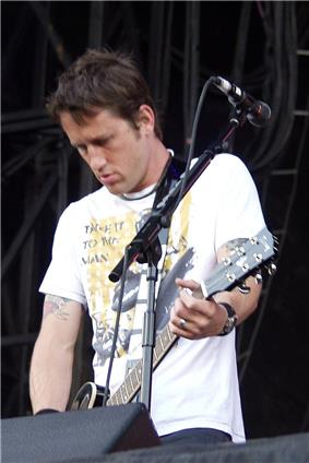 A man in a white shirt plays a guitar atop a stage.