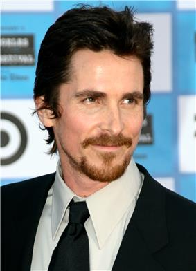 Close-up image of a man. His brown hair is short and he has a beard and mustache. He wears a black tux and black tie.
