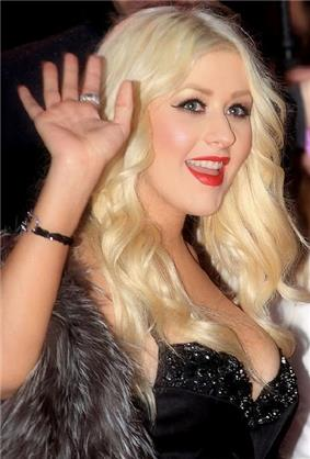 A blonde-haired woman is waving her hand
