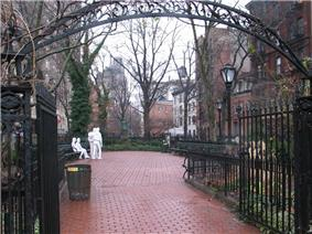A color photograph of Christopher Park in winter, showing the wrought iron entrance arch in the foreground and the brick pavement surrounded by five and six story brick buildings; in the center background are four white statue figures: two males standing, one with his hand on the other's shoulder, and two females seated on a park bench, one woman with her hand touching the other's thigh. All are dressed in jeans and loose clothing