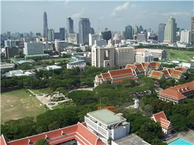 The campus of Chulalongkorn University, with many red-roofed buildings and trees; many tall buildings in the background