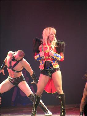 Image of a blond woman. She wears a red circus ringleader jacket with feathers, shorts and stockings. She holds a whip around her neck. In the woman's left, there's a man dressed in S&M bondage clothing.