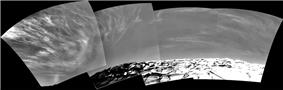 A composite black-and-white photograph showing cirrus clouds over the surface of Mars.