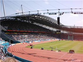 A fully occupied grandstand on a sunny day. In front of it is an athletics track.