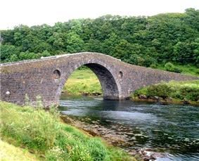 An arched stone bridge crosses a small body of water leading to woodlands in the background