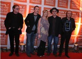 Five people (four men, one woman in the middle) standing next to one another on a red carpet; in the background is a repeated pattern of orange blocks with the text