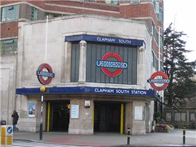 A light-grey-tiled building with a blue sign reading