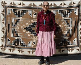 Clara Sherman standing in front of her woven Navajo rug