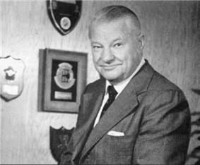 Black-and-white portrait photograph of gray-haired man in suit posing to the right; a number of plaques are present on the wall behind.