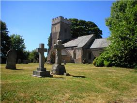 Stone building with square tower. In the foreground are stone crosses, gravestones and trees.