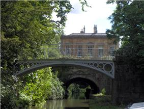 A iron bridge spanning water. In the background is a yellow stone building. On the left trees reach out over the water.