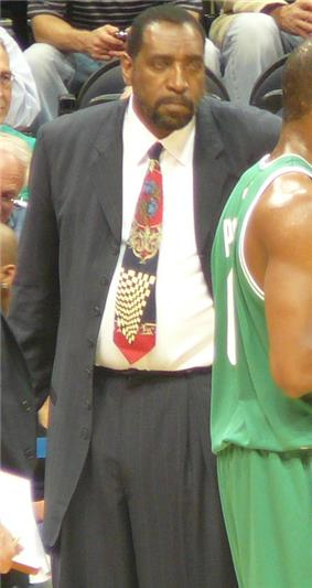 A black person, wearing a black suit and a tie, is standing beside a basketball player in front of the spectators.