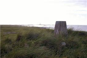 A small concrete pillar sits amongst long grass. There is a body of water in the background.