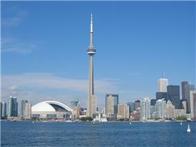 A spear-like tower is between a white-domed structure and small buildings on the left, and increasingly taller buildings to the right.  In the foreground is a lake, with a few visible buoys, and the background is a deep blue sky with a few clouds near the horizon.