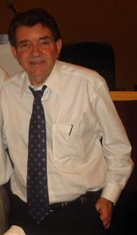 A man standing with his hands in his pockets. He is wearing a white shirt with a dark patterned tie.