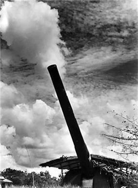 A large calibre gun fires, creating a cloud of smoke