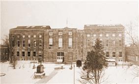 A sepia-toned photograph of a large, rectangular building.