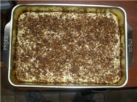 A whole coffee cake still in a baking pan and topped with chopped nuts