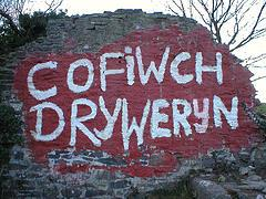 a ruined wall, splashed with red paint, upon which in white paint is written the words 'cofiwch Dryweryn'