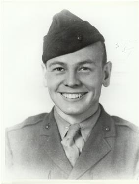 Head and shoulders of a young white man with a broad smile. He is wearing a garrison cap tilted over his right ear and a plain military jacket on top of a shirt and tie.