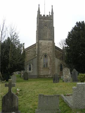 Stone building with prominent square tower at near end. In the foreground are gravestones and trees to the left and right.