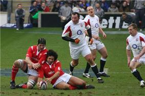 Two Wales' players falling onto a grounded ball while three England players approach their position.
