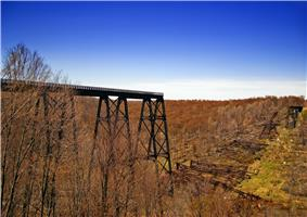 A trestle bridge across an autumnal valley at left ends in a drop off at center, with collapsed remnants at right, all under a bright blue sky