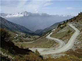 Photo of a mountain pass in the foreground, the steep road leading up to it and mountains on the horizon.
