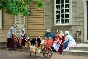 Five women dressed in long colonial style clothing sit on the stairs of tan and beige buildings talking. In front of them is a wooden wheelbarrow full of wicker baskets.