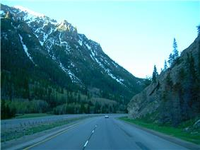 A highway about to curve to the right while descending down a canyon