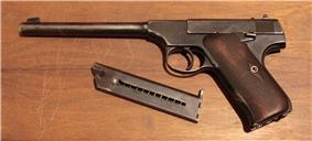 An early first series Colt Woodsman pistol and magazine.