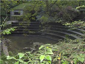 Semicircular stone steps, partially obscured by trees. Water to the left
