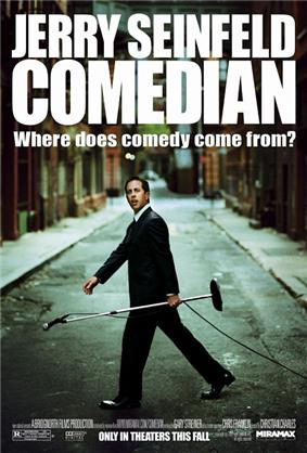 Jerry Seinfeld walking along a street carrying a microphone stand