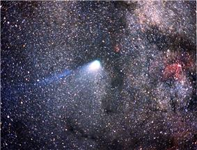 Halley's Comet, tail barely visible, against a background of stars. The Milky Way is seen in the background.