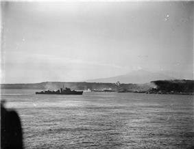 A black and white photograph showing a warship firing its armament at positions on the foreshore, while in the distance landing craft move towards the beach