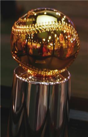 A golden baseball sitting atop a silver pedestal